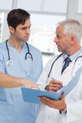 Serious doctors talking about file - stock photo