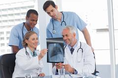 Smiling medical team examining radiography - stock photo
