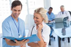 Stock Photo of Two smiling doctors talking about a blue file