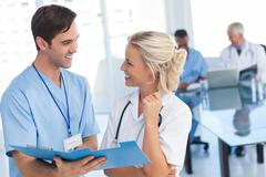 Two young doctors talking about a blue file - stock photo
