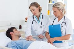 Two women doctors talking  to a patient - stock photo