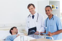 Doctors with radiography standing next to a patient Stock Photos