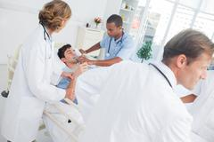 Doctors taking care of a sick patient - stock photo