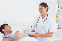 Stock Photo of Attractive nurse measuring the blood pressure of a patient