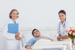 Stock Photo of Doctors and patient looking at the camera