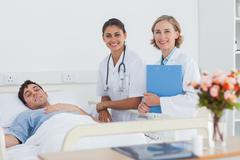 Stock Photo of Two doctors and a patient looking at the camera