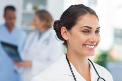 Smiling doctor standing in front of a medical team - stock photo