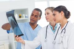Medical team analysing an x-ray Stock Photos