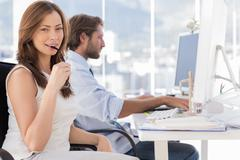 Woman biting her glasses with colleague working behind Stock Photos