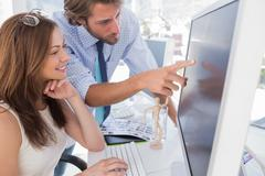 Man pointing something to his partner on screen Stock Photos