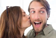 Stock Photo of Woman kissing man with beard on the cheek