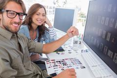 Two smiling photo editors working with contact sheets - stock photo
