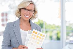 Stock Photo of Pretty interior designer holding up colour samples