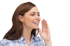Smiling woman placing her hand to say something - stock photo