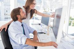 Stock Photo of Photo editors looking at computer screen with one pointing