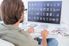 Photo editor viewing thumbnails on computer - stock photo