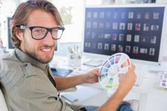Photo editor looking at colour wheel and turning to smile - stock photo