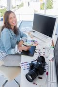 Stock Photo of Laughing photo editor working with a graphic tablet