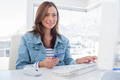 Cheerful woman purchasing online with her credit card - stock photo