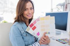 Smiling interior designer holding up colour samples Stock Photos