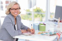 Stock Photo of Cheerful interior designer working on colour charts