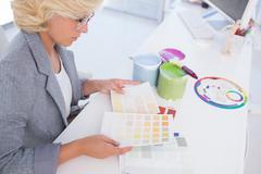 Serious interior designer looking at colour charts Stock Photos