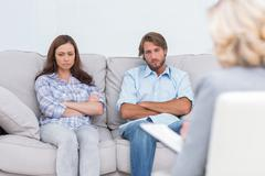 Upset couple sit on a sofa with arms crossed - stock photo