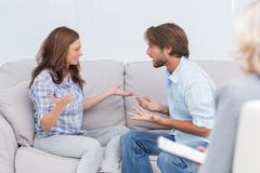 Couple arguing while the therapist is listening to them Stock Photos