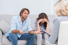 Young couple arguing and crying on the couch Stock Photos