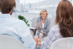 Smiling psychologist talking to a couple - stock photo