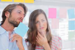 Two colleagues looking at sticky notes Stock Photos