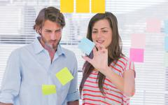 Woman showing the sticky note to her colleague Stock Photos