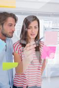 Woman showing sticky note to her colleague Stock Photos