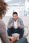 Upset man speaking to a therapist Stock Photos