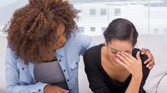 Sad woman crying next to her therapist - stock photo