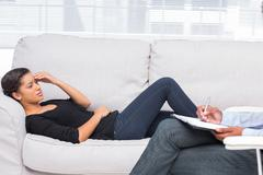 Woman getting distressed in therapy - stock photo