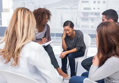 Woman getting distressed in group therapy - stock photo