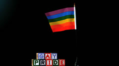 Rainbow flag blowing in the breeze beside gay pride blocks on black background Stock Footage