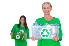 Pretty enivromental activists holding box of recyclables Stock Photos