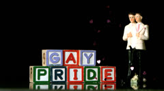 Confetti falling on blocks spelling gay pride with gay cake topper Stock Footage