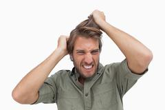 Frustrated man pulling his hair - stock photo