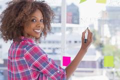 Woman drawing on flowchart with sticky notes and smiling at camera Stock Photos
