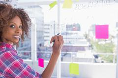 Stock Photo of Woman drawing on flowchart with marker and smiling at camera
