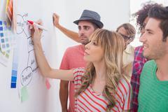 Creative team watching coworker add to flowchart - stock photo