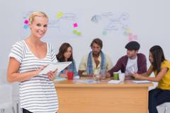 Happy editor using tablet pc as team works behind her - stock photo
