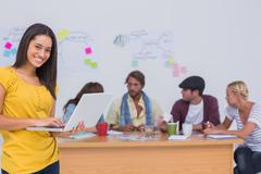 Prettty editor using laptop as team works behind her - stock photo