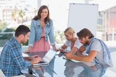 Team having meeting with one woman smiling at camera - stock photo