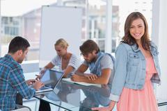 Stock Photo of Team having meeting with one woman standing and smiling at camera