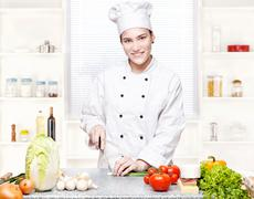 young chef cutting onions in kitchen - stock photo