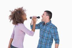 Fun duo singing to each other at karaoke - stock photo
